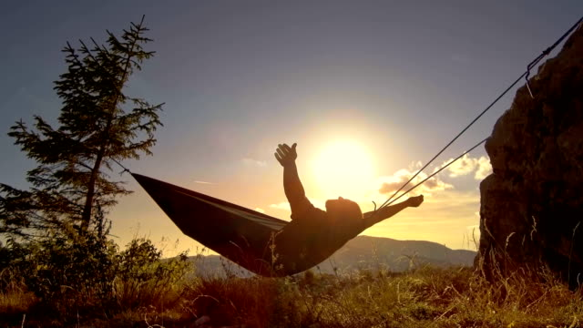 man relaxing in hammock at sunset in the mountains - amaca video stock e b–roll