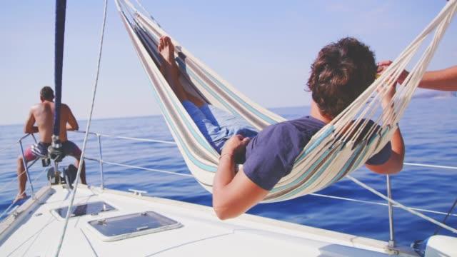 vídeos y material grabado en eventos de stock de hombre relajante en hamaca, bebiendo cerveza en velero soleado, tiempo real - yacht