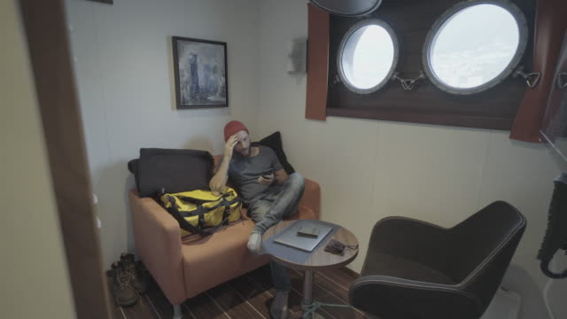Man relaxing in the cabin of a sailing vessel: social distancing isolation
