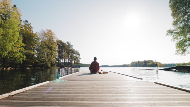 Man relaxing on a jetty after exercising outdoors A man is walking out on a jetty on a lake to relax after exercising. He has an exercise mat and a protein shake with him. jetty stock videos & royalty-free footage