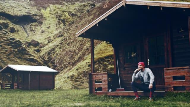 mann auf der kabine veranda entspannen. betrachten - blockhütte stock-videos und b-roll-filmmaterial