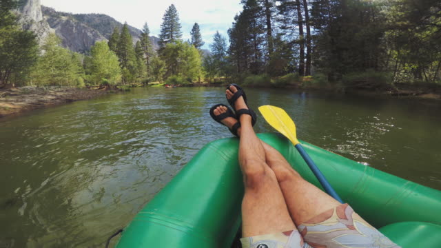 POV man relaxing while rafting in Merced River of Yosemite POV of a man rafting in Merced River of Yosemite cross legged stock videos & royalty-free footage