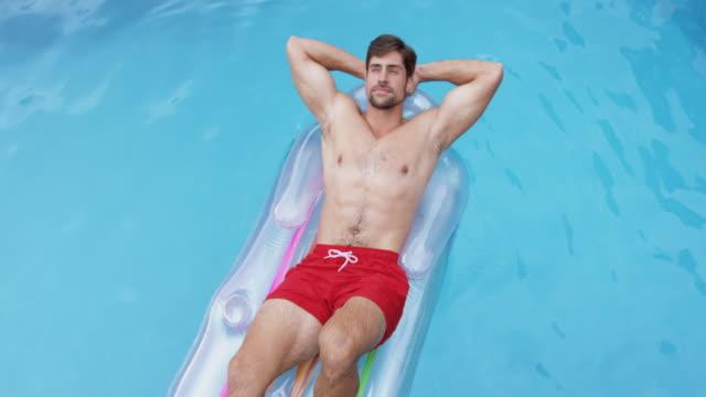mann entspannen daniert mit denk hinter kopf auf aufblasbare röhre im schwimmbad 4k - nackter oberkörper stock-videos und b-roll-filmmaterial