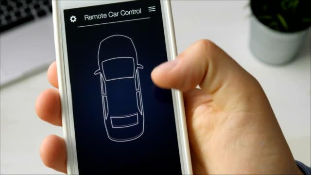 stockvideo's en b-roll-footage met man op afstand zijn auto parkeren. auto-afstandsbediening met behulp van fictieve toepassingsinterface smartphone. - parkeren