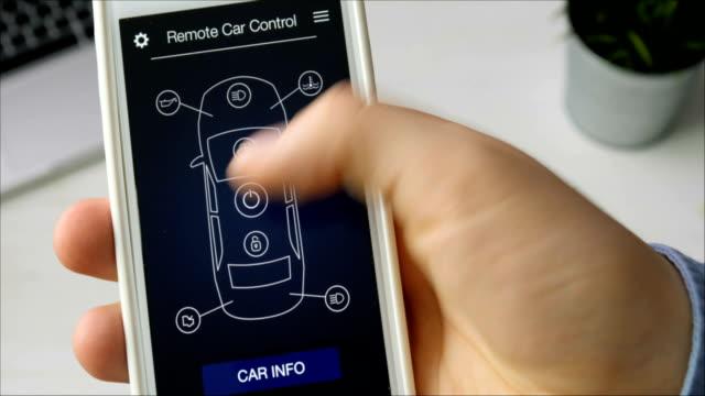 男は、彼の車のエンジンをリモートで開始します。車のリモコンがスマート フォン アプリケーション架空インターフェイスを使用します。 - 人里離れた点の映像素材/bロール