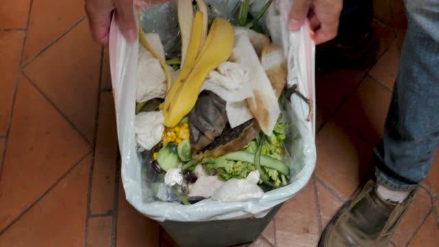 Man removes a plastic bag of trash from a kitchen plastic garbage bin Man removes a plastic bag of trash from a kitchen plastic garbage bin filled with mostly organic food scraps and paper - overhead shot leftovers stock videos & royalty-free footage