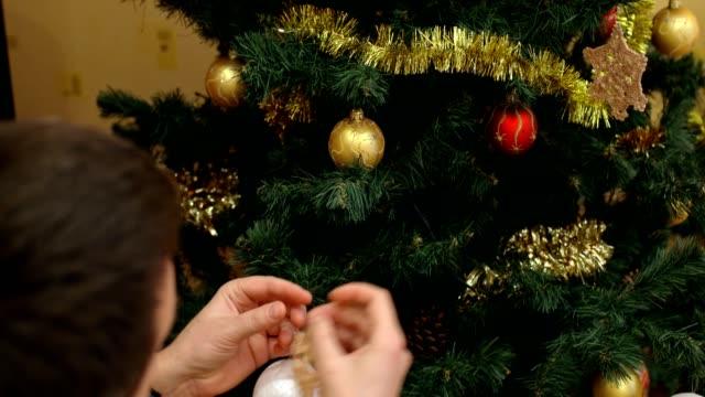 ein mann entfernt weihnachtsspielzeug von einem baum in seinem haus - girlande dekoration stock-videos und b-roll-filmmaterial