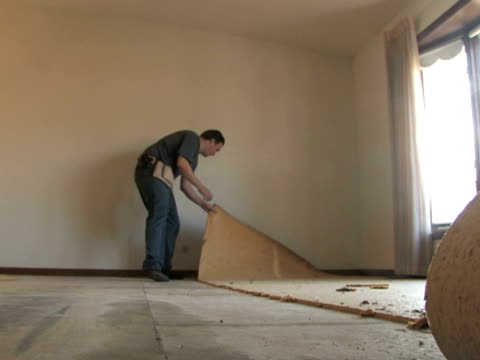 Man Removing Carpet A handyman tears up carpet padding from the floor padding stock videos & royalty-free footage