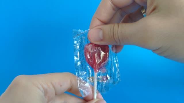 人刪除心臟形狀的棒棒糖包裝。情人節概念 - 波板糖 個影片檔及 b 捲影像