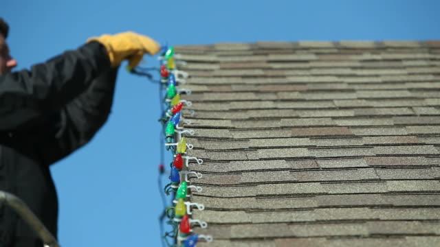Mann, Entfernen von LED-Lichterkette von einem Haus Dach – Video