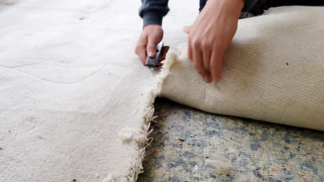 man removing old carpet from floor - moquette video stock e b–roll