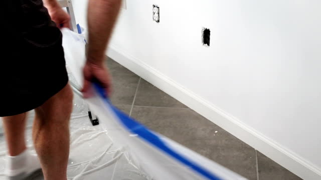 Man Removing Painter s Tape and Plastic Tarp After Painting video