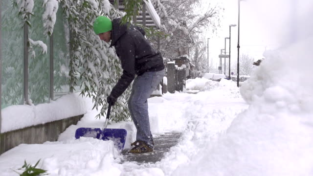 SLOW MOTION: Man removing snow from a sidewalk video