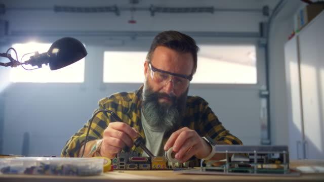 vídeos de stock, filmes e b-roll de slo mo man reparando uma placa de circuito soldando-a em sua oficina - hobbie