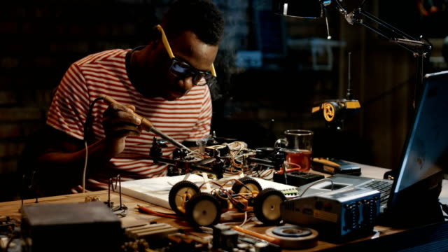 Man repairing a drone Slow motion shot of a black man repairing a drone in a garage hobbies stock videos & royalty-free footage
