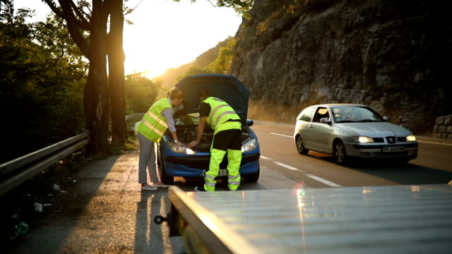 vídeos de stock e filmes b-roll de man repairing car on the road - resgate