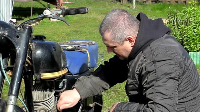 Man repairing old motorcycle at outdoor video