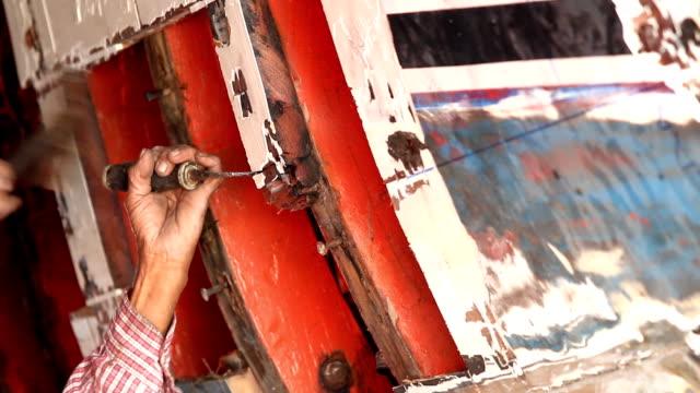 stockvideo's en b-roll-footage met een man die herstellen van houten boot - lood