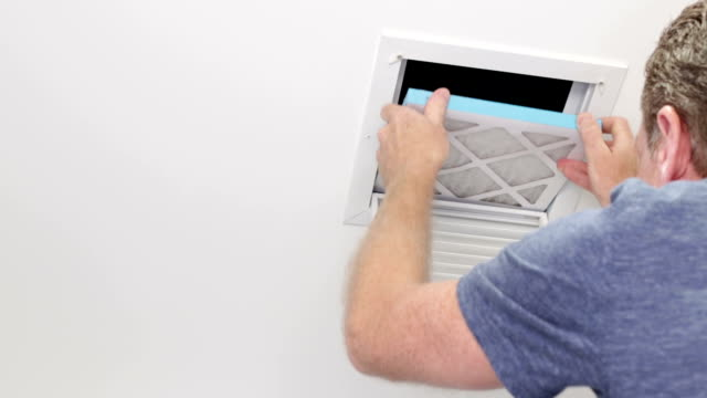 Man Replacing a Small Ceiling Air Filter