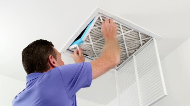 Man Replacing Ceiling Air Filter Mature male replacing a dirty air filter with a clean one in a HVAC return duct. Technician changing a dirty air filter for a clean one in a ceiling home air duct. positioning stock videos & royalty-free footage