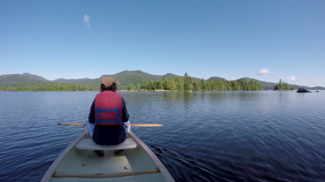 Man resting in a canoe on a lake as the clouds overhead reveal full sunlight