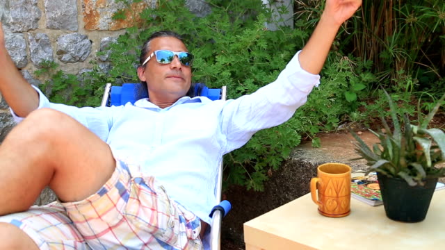 Man resting in the garden and drinking coffee Man resting in the garden and drinking coffee mid adult men stock videos & royalty-free footage