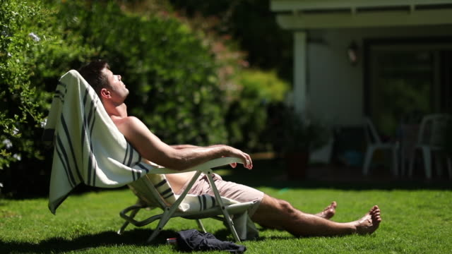 Man resting outside sunbathing in backyard home. Person taking a break napping outdoors Man resting outside sunbathing in backyard home. Person taking a break napping outdoors sunbathing stock videos & royalty-free footage