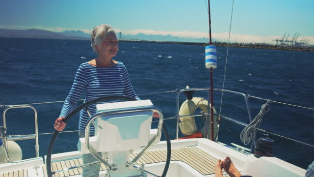 Man resting while woman steering yacht in vacation