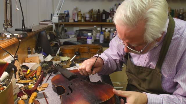 Man Restoring Violin In Workshop video