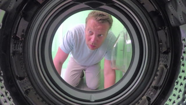 pov of man retrieving sock from washing machine - calzino video stock e b–roll