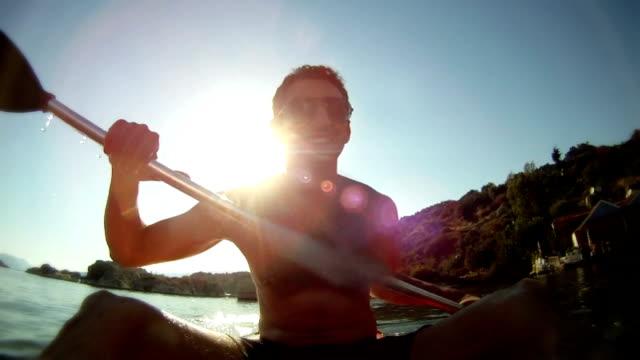 Homme de manière rythmique kayak dans le soleil - Vidéo