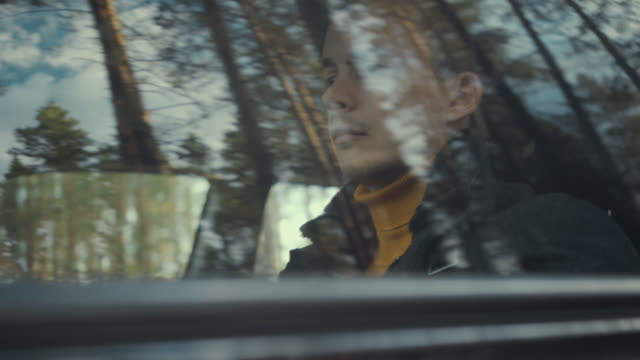 男は田舎道で車に乗る。車の窓に映る木々 ビデオ