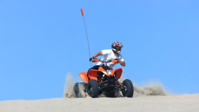 Man riding a quad in sand, time ramp, slow motion video