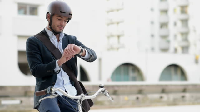 Man riding bicycle on city street using tablet and smart watch Man riding bicycle on city street using tablet and smart watch work helmet stock videos & royalty-free footage