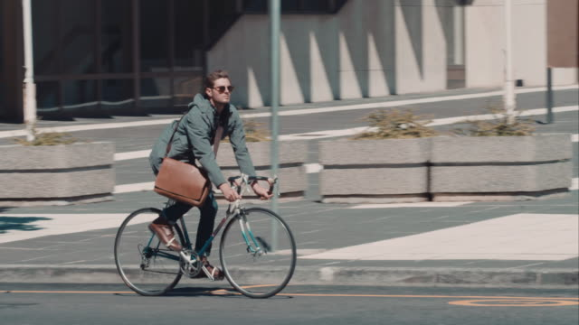 Man riding bike in urban setting video