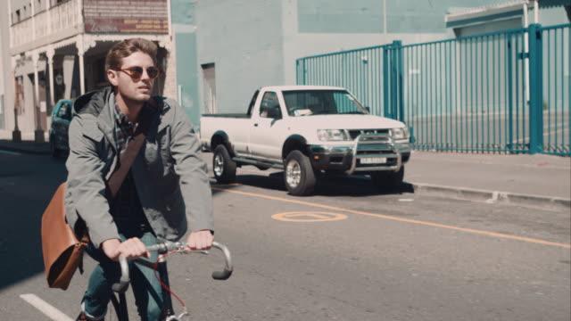 Man riding bike in urban setting video