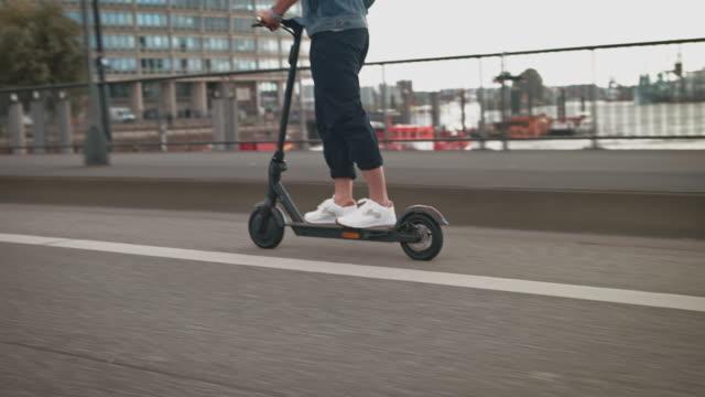 man riding electric push scooter on bridge - monopattino elettrico video stock e b–roll
