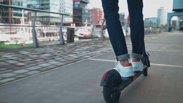 uomo in sella a uno scooter elettrico push sul sentiero - monopattino elettrico video stock e b–roll
