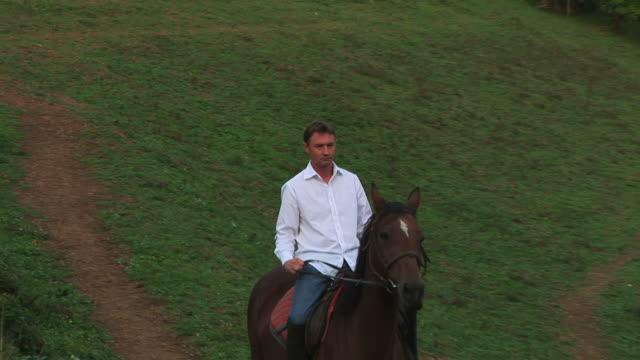 stockvideo's en b-roll-footage met man riding horse in nature - alleen één mid volwassen man