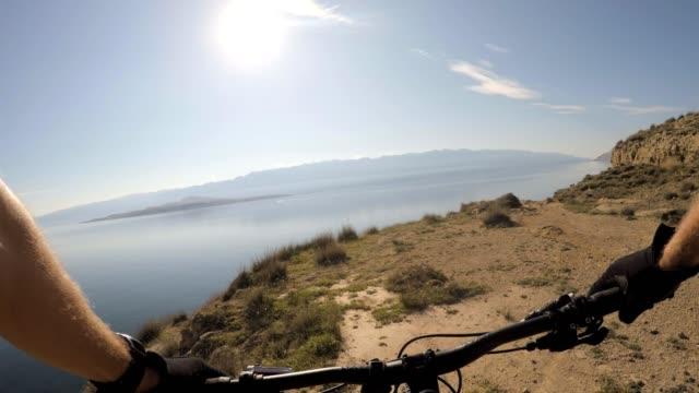 man riding mountain bike, cycling on rocks personal perspective view - percorso per bicicletta video stock e b–roll
