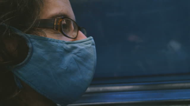 man riding on a subway train wearing a protective respiratory face mask - contagi video stock e b–roll