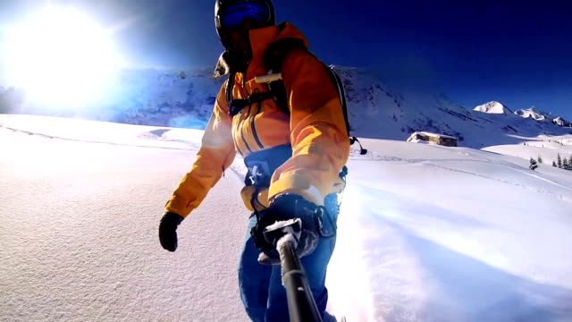 man riding on snowboard with selfie stick in his hand - snowboarding video stock e b–roll