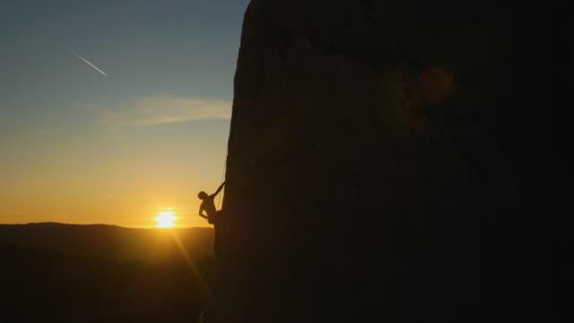 man rock climbing at amazing sunset - альпинизм стоковые видео и кадры b-roll