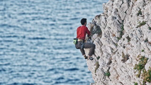 Pedra do homem subindo em uma parede do penhasco áspero - vídeo