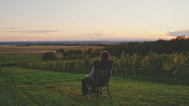 Man rocking in rocking chair in lawn overlooking idyllic rural sunset landscape, real time 4K Man rocking in rocking chair in lawn overlooking idyllic rural sunset landscape. WS, real time. rocking chair stock videos & royalty-free footage