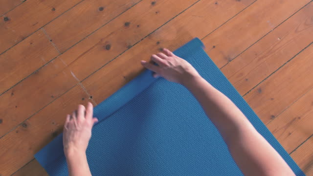 man rolling out yoga mat at home - tappetino video stock e b–roll