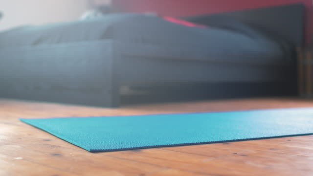 Man rolling out Yoga mat at Home Young man rolling out a yoga mat at home. Low angle shot in 4K resolution. rolling stock videos & royalty-free footage