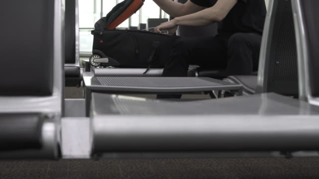 Man rolling Suitcase wheels inside airport video