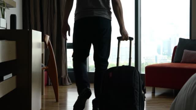 mężczyzna toczenia koła walizki do hotelu - odejście filmów i materiałów b-roll