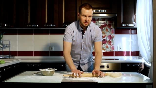 vidéos et rushes de l'homme roule la pâte sur la table de la cuisine avec un rouleau à pâtisserie. - boulanger